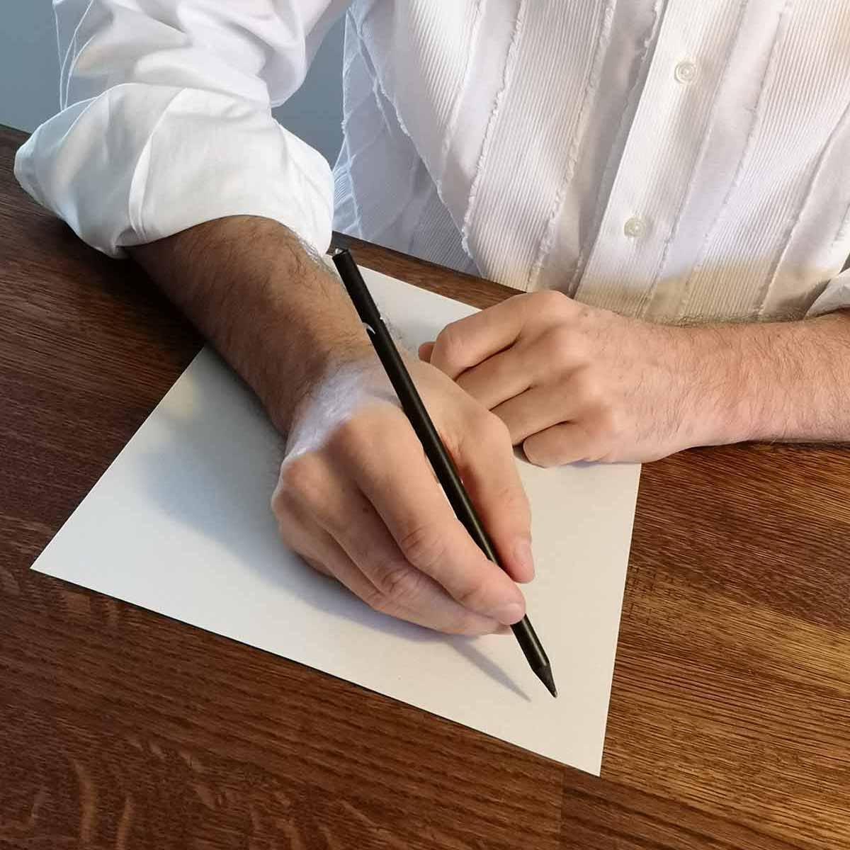Person sitzt auf Schreibtisch und schreibt
